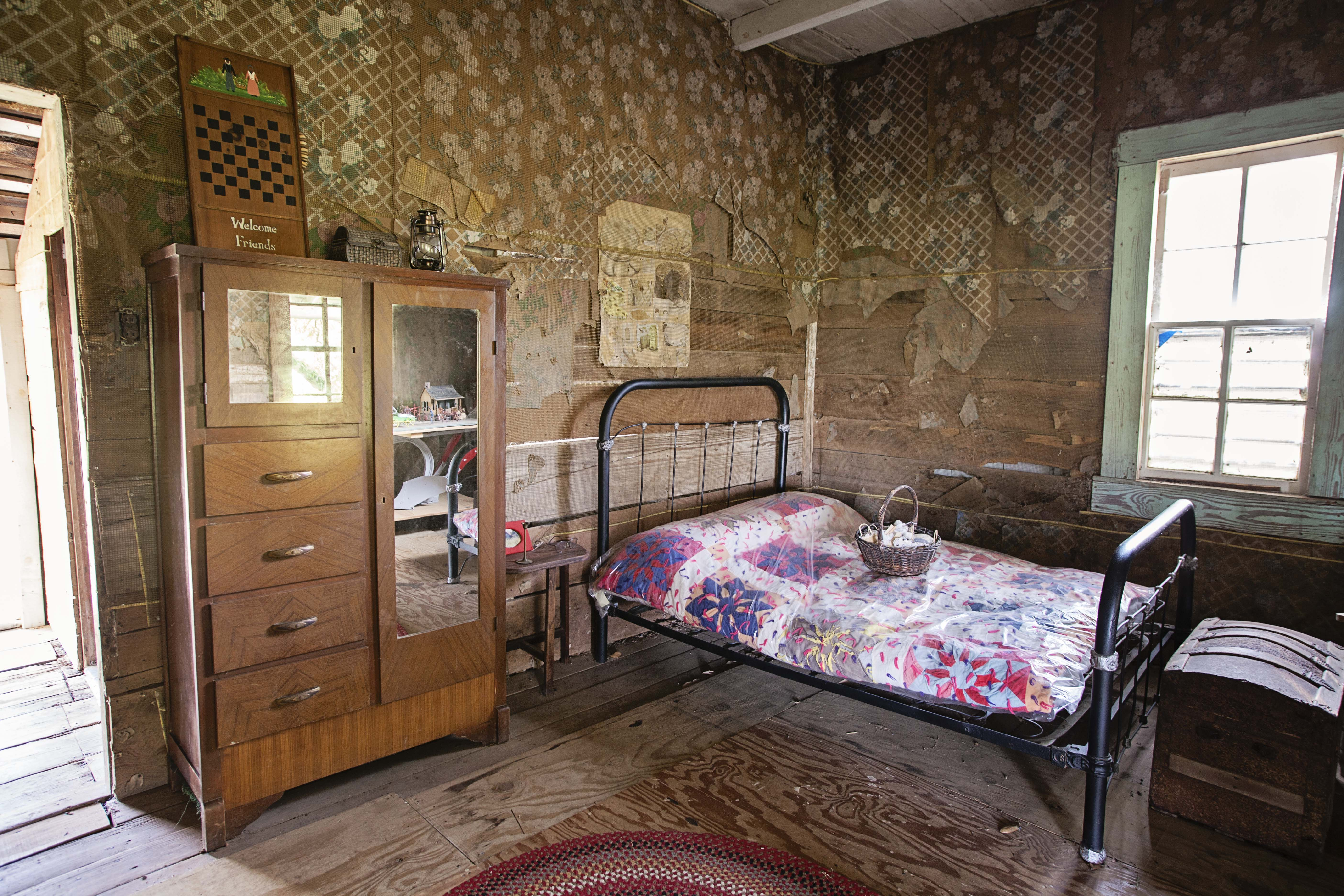 Across from the fireplace, in the cabin's main room, is a small bed with a brightly colored quilt. Beside the bed stands a wardrobe and a large truck sits at the foot of the bed.