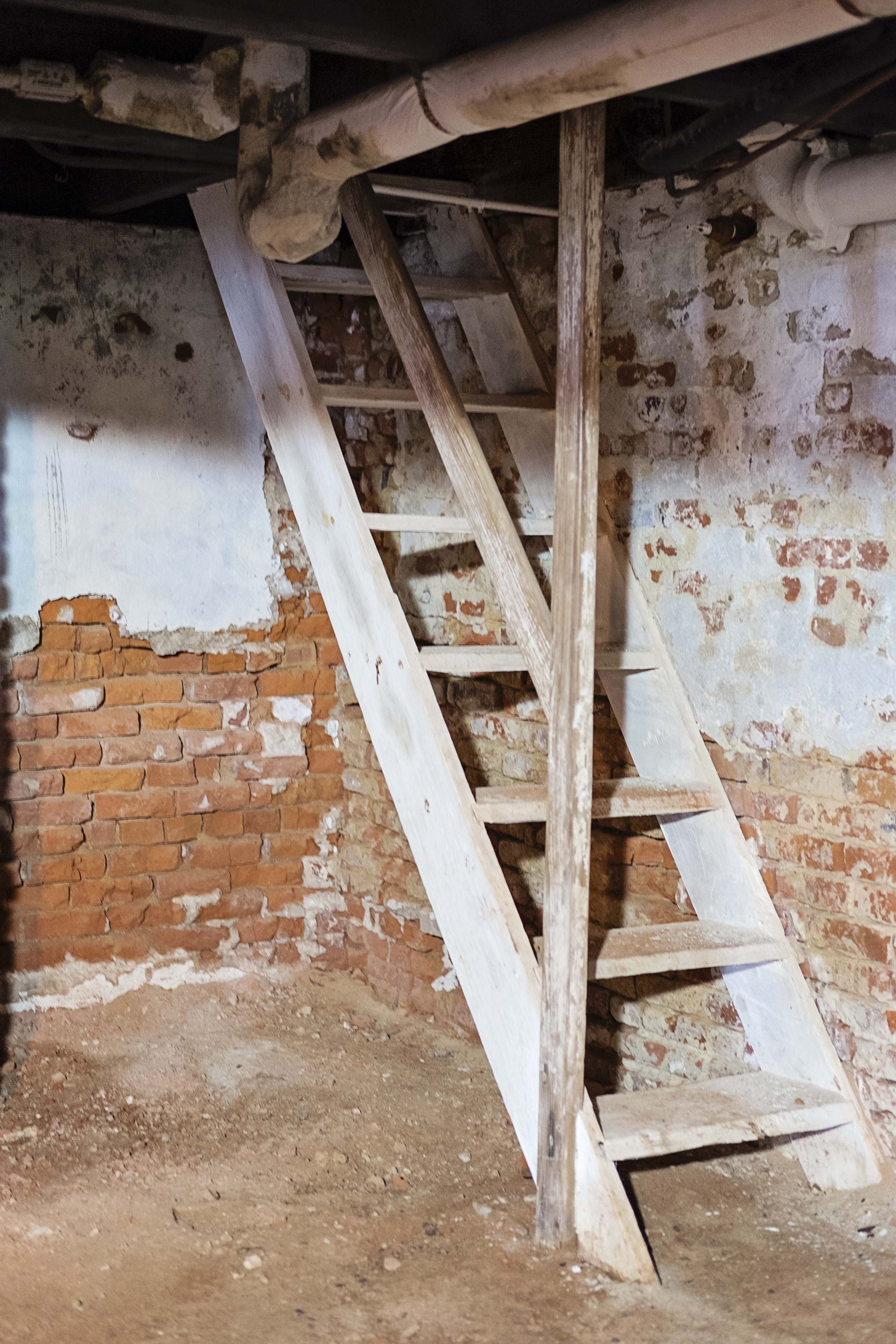 A small brick room on the lower level of the house served as the enslaved nanny's room. She would climb these wooden stairs in the corner of the room to enter the Prud'homme children's room above.