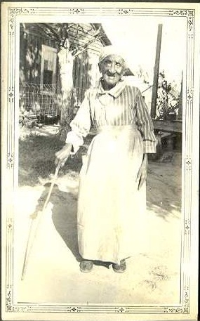 An elderly women, Marie stands with a cane.