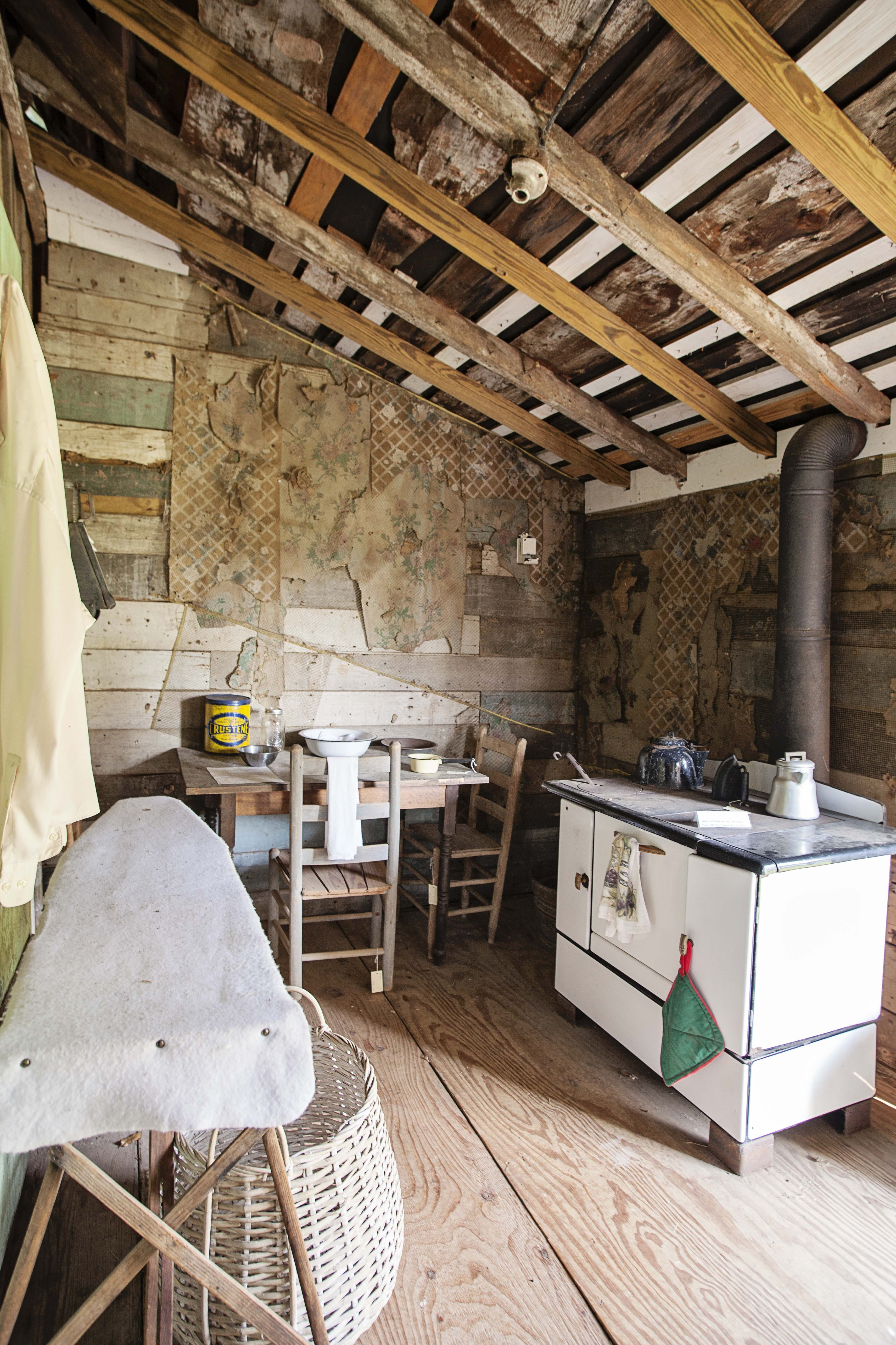 Small cabin porch that was enclosed to add an additional room. Serving as a kitchen with a stove, small table with chairs and an ironing board.
