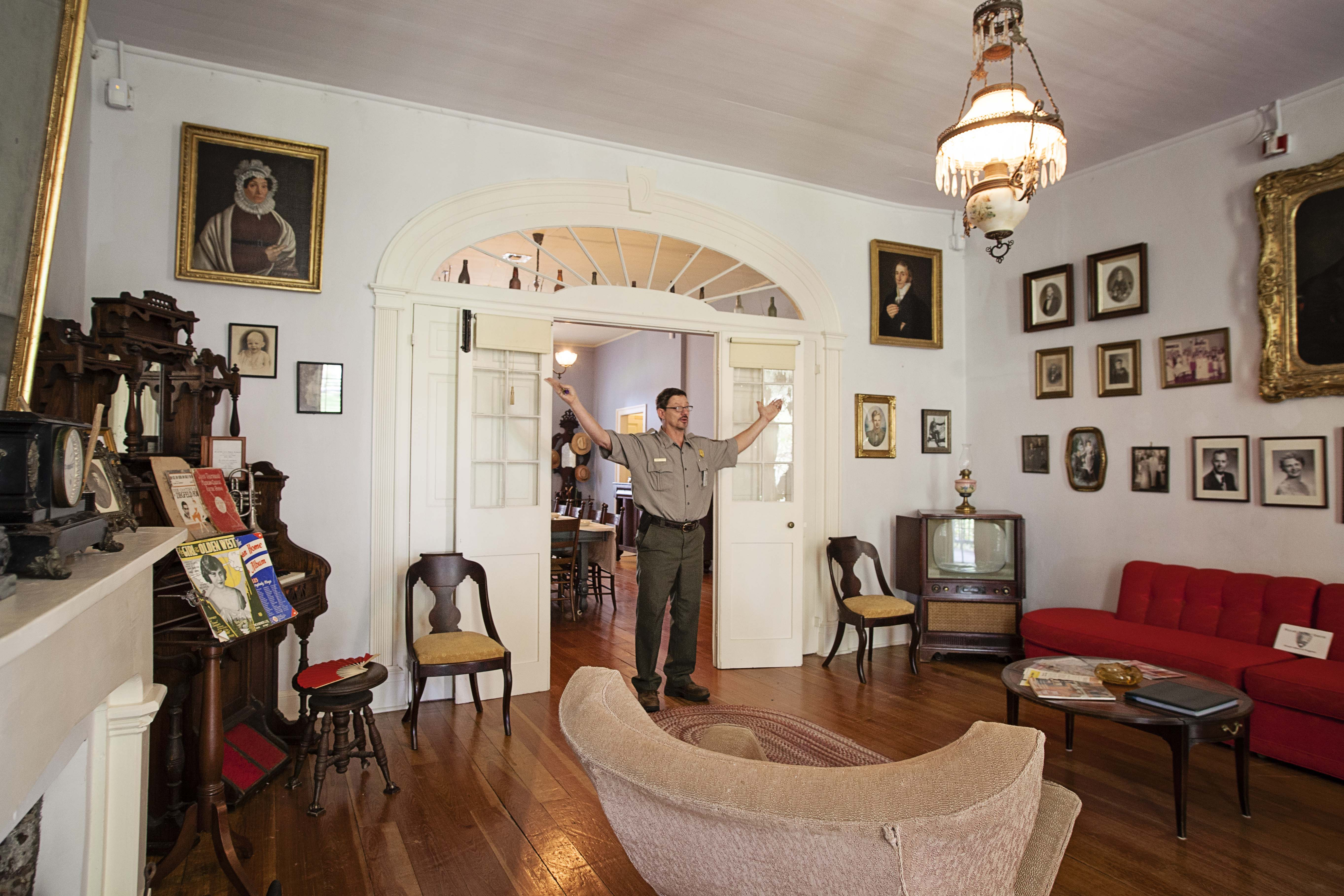 A park ranger stands in the Parlor of the Main House. Behind the ranger are double doors, over which is a large fan light, leading to the Dining Room.