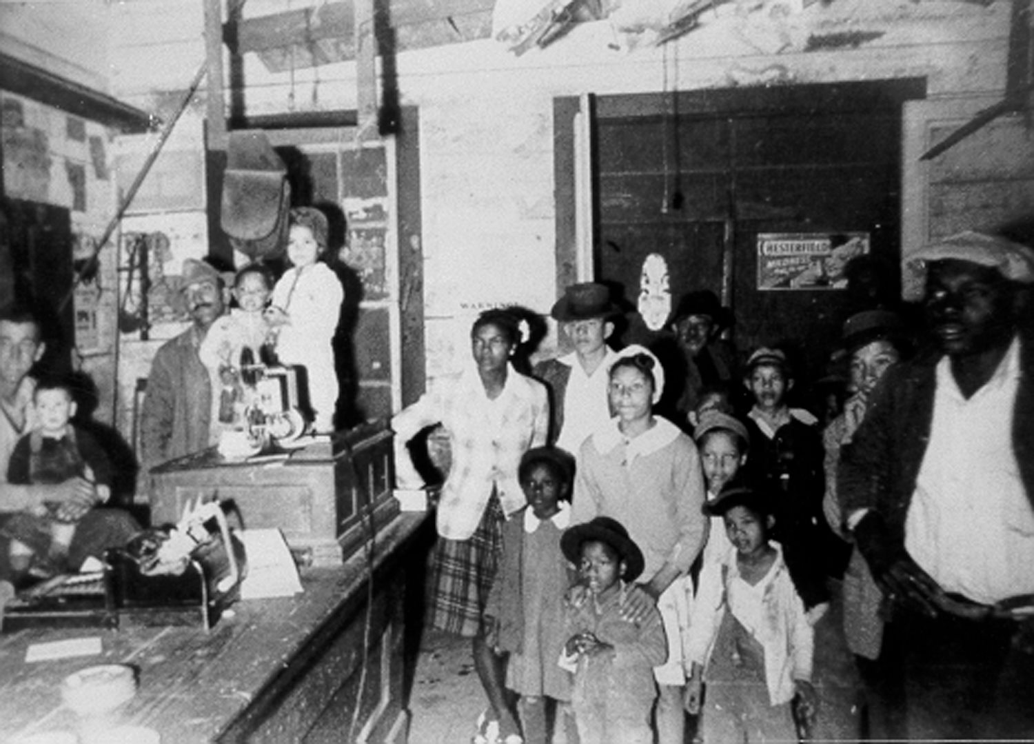 A group of adults and children stand inside the Magnolia Plantation Store in the 1940s. A movie projector stand on the store counter.